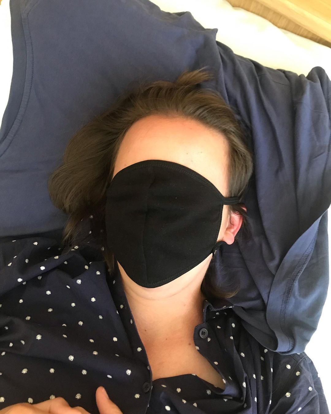 a figure laying on a navy blue pillow, over their face is a black face mask that, instead of covering the nose and mouth, also coviers their face, leaving thier forehead exposed. Their dark hair and dotted shirt lay crumpled on the pillow