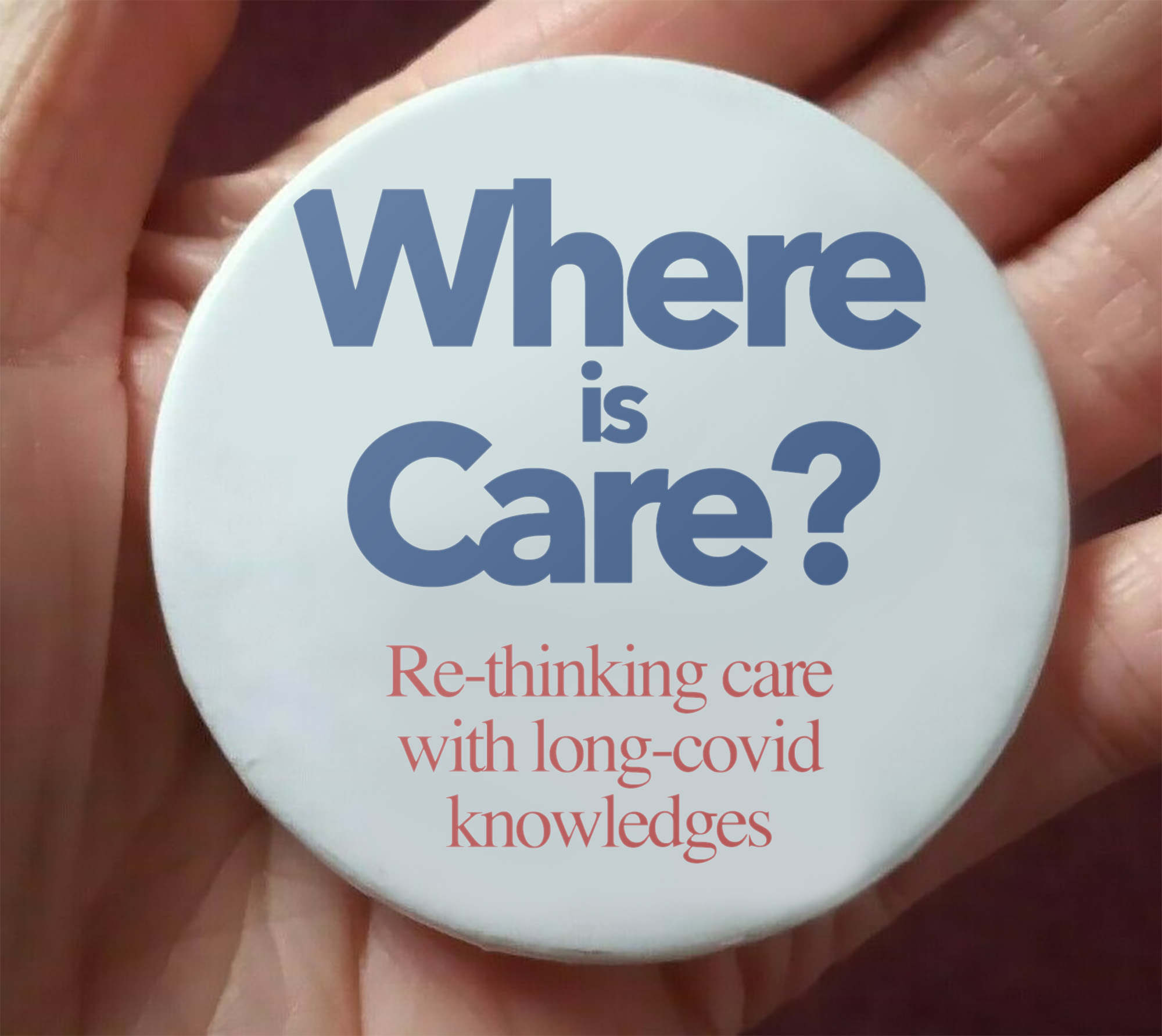 A badge on a hand that states 'Where is care? Re-thinking care with long-covid knowledges